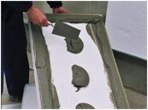 Нанесение клея на тыльную сторону плиты из пенопласта