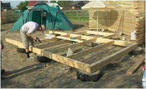 Процесс возведения постройки на покрышках.
