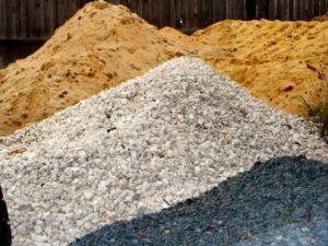 Песок и щебенка, готовые к засыпке